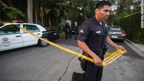 A police officer creates a perimeter outside the Los Angeles home of Andrew Getty, heir to the Getty oil fortune.