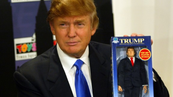 Trump poses with the new Donald Trump 12-inch talking doll on September 29, 2004, at the Toys