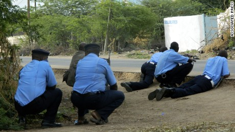 Kenyan police officers take cover outside Garissa University College on Thursday.
