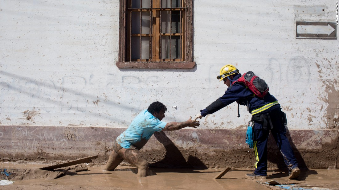 A rescue worker stretches his hand to help a local resident cross a street in Chanaral on March 27.
