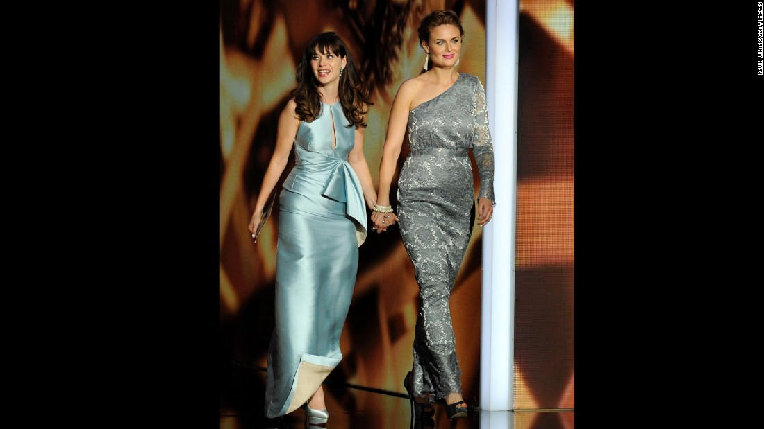 "Sisters Zooey Deschanel, left, of ""The New Girl"" and Emily Deschanel of ""Bones"" hold hands at the Emmy Awards in 2013."