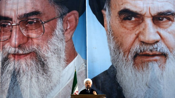 Iranian President Hassan Rouhani delivers a speech under portraits of Iran's supreme leader, Ayatollah Ali Khamenei (L) and Iran's founder of the Islamic Republic, Ayatollah Ruhollah Khomeini (R), on the eve of the 25th anniversary of the Islamic revolutionary leader Ayatollah Ruhollah Khomeini's death, at his mausoleum in a suburb of Tehran on June 3, 2014. AFP PHOTO / ATTA KENARE (Photo credit should read ATTA KENARE/AFP/Getty Images)