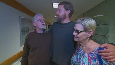 Louis Jordan, center, stands with his parents after what he says were 66 days drifting alone in the Atlantic Ocean.