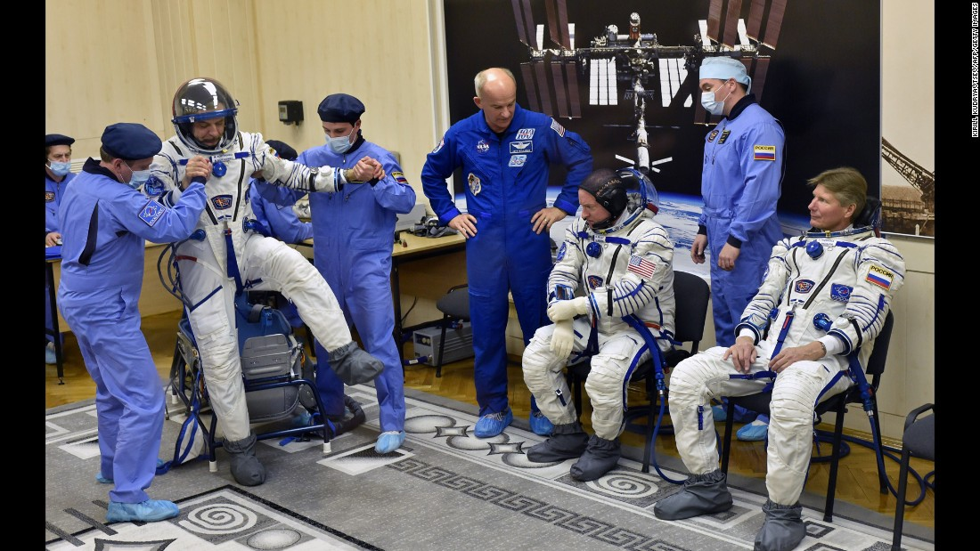 Kornienko tests his spacesuit as Kelly and Padalka wait their turn on March 27.
