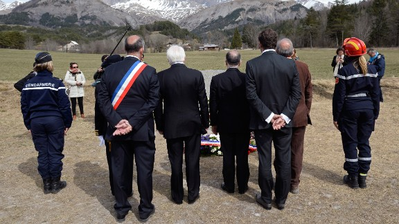 """French government officials observe a moment of silence for <a href=""""http://www.cnn.com/2015/03/24/world/gallery/france-plane-crash/index.html"""" target=""""_blank"""">Germanwings Flight 9525</a> near the crash site Friday, April 3, in Le Vernet, France."""