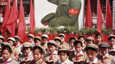 A group of Chinese children in uniform hold Mao's 'Little Red Book' during China's Cultural Revolution.