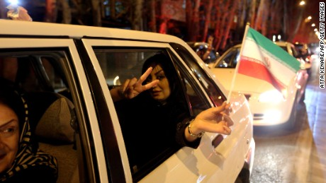 A woman in a car flashes the 'V for Victory' sign and waves an Iranian flag as people celebrate on Valiasr street in northern Tehran on April 2, 2015, after the announcement of an agreement on Iran nuclear talks. Iran and global powers sealed a deal on April 2 on plans to curb Tehran's chances for getting a nuclear bomb, laying the ground for a new relationship between the Islamic republic and the West. AFP PHOTO / ATTA KENARE (Photo credit should read ATTA KENARE/AFP/Getty Images)