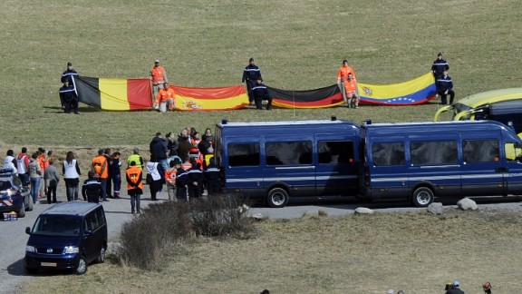 Relatives of the Germanwings Flight 9525 crash victims arrive on Saturday, April 4, at a ceremony as rescuers hold flags of the late passengers