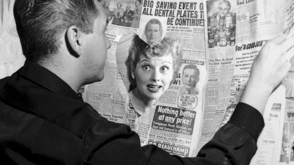 Ball looks at Arnaz through a heart cut out in a newspaper. The couple married in 1940 and divorced 20 years later.