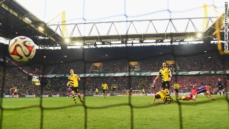 Robert Lewandowski falls to the ground after giving Bayern Munich the lead against Borussia Dortmund.