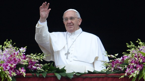 Pope Francis greets the crowd from the central loggia of St Peters' basilica after the 'Urbi et Orbi' blessing for Rome and the world.