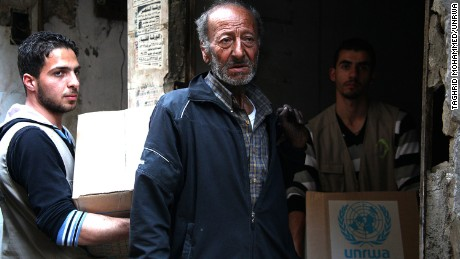 Palestinians at the Yarmouk refugee camp in Syria receive supplies from the United Nations Relief and Works Agency on March 9.