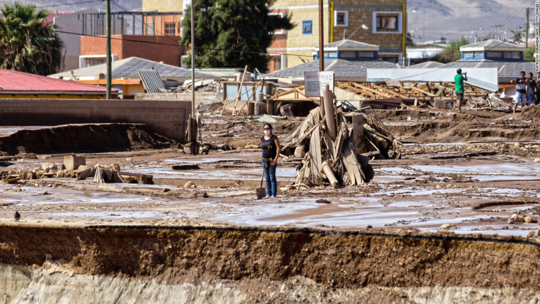 A woman stands in the muddy ruins of a flooded street in Chanaral, Chile, on April 1, after heavy rainfall caused the overflowing of the Copiapo River.