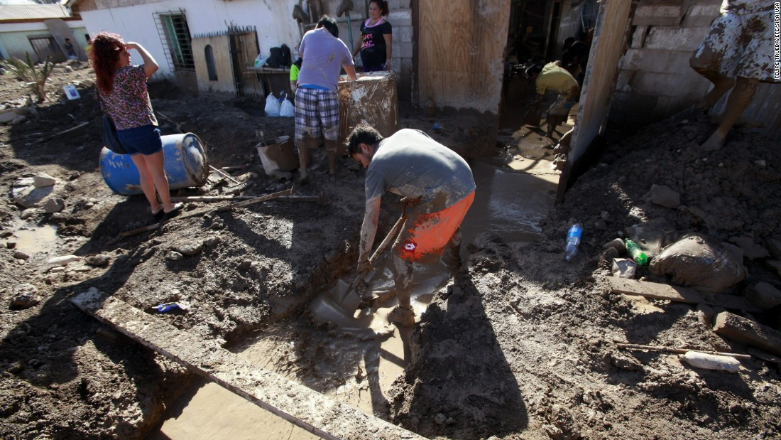 Residents shovel mud from a home in Diego de Almagro, Chile, on Saturday, March 28.