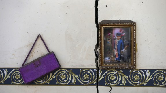 A framed photo and a purse hang on the wall of a house destroyed by an airstrike near the Sanaa airport on Tuesday, March 31.