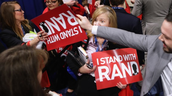 """Paul supporters are handed placards reading """"I Stand with Rand"""" while waiting in line for a book signing with the senator at the Conservative Political Action Conference."""