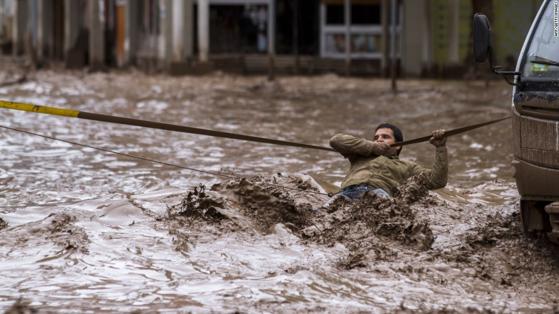 A man clings to a security line while crossing a flooded street in Copiapo on Thursday, March 26.