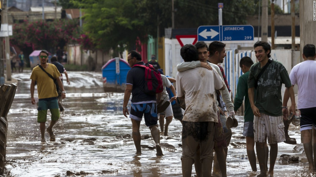 People walk along a flooded street in Copiapo on March 26.