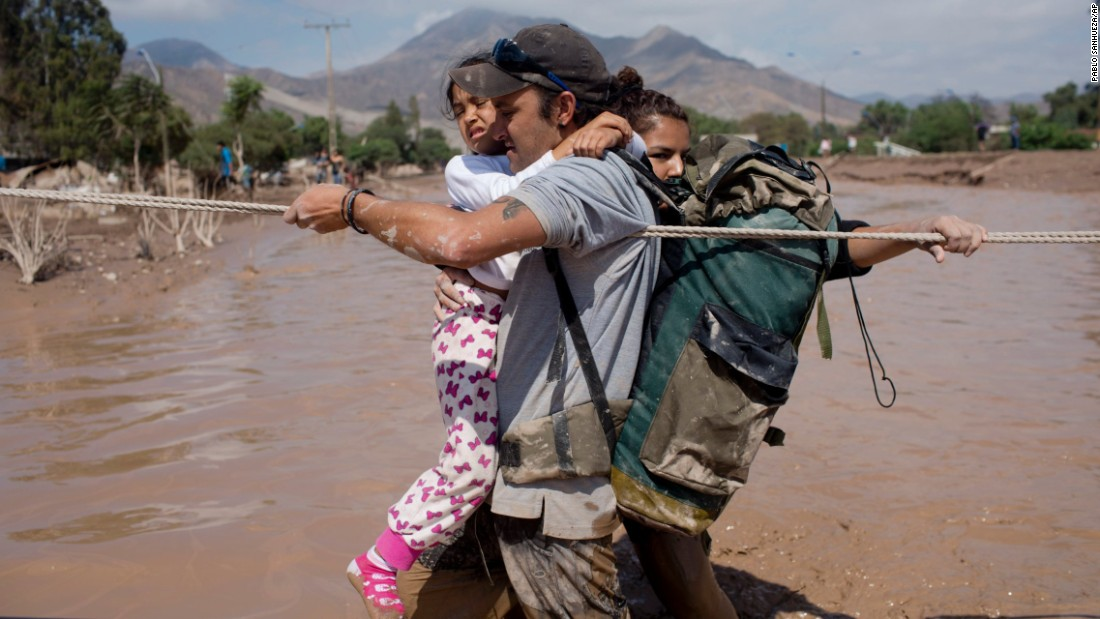 A family holds onto a rope as they cross a flooded street in Copiapo on March 26.