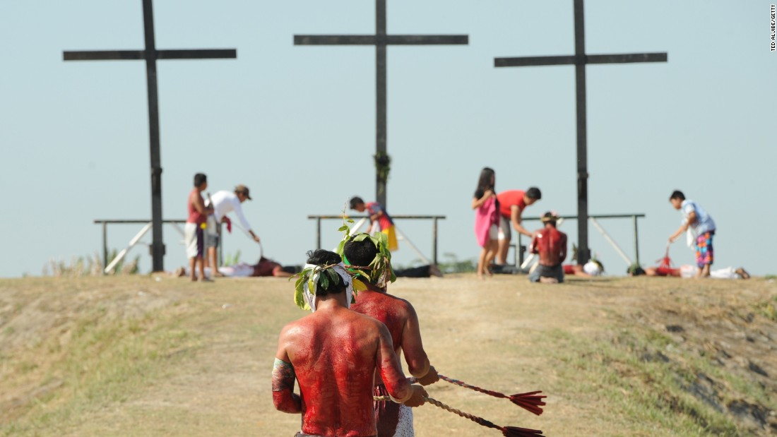 Penitents walk towards crosses as they whip themselves on April 3, 2015.