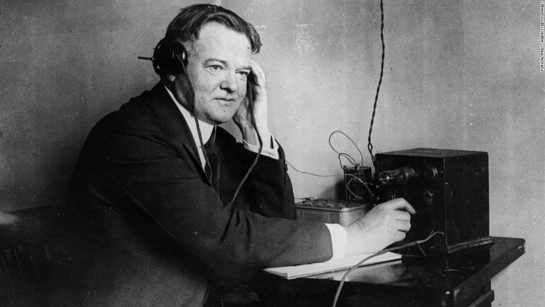 "Herbert Hoover listens to a one-valve radio set circa 1928. Hoover's campaign slogan in 1928 was, ""A chicken in every pot and a car in every garage."""