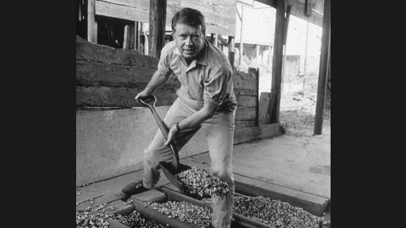 """Jimmy Carter looks up while shoveling peanuts on a peanut farm sometime in the 1970s. Carter was a peanut farmer, and """"Not Just Peanuts"""" was one of his campaign slogans during the 1976 presidential election."""