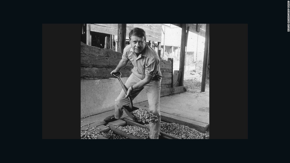 "Jimmy Carter looks up while shoveling peanuts on a peanut farm sometime in the 1970s. Carter was a peanut farmer, and ""Not Just Peanuts"" was one of his campaign slogans during the 1976 presidential election."
