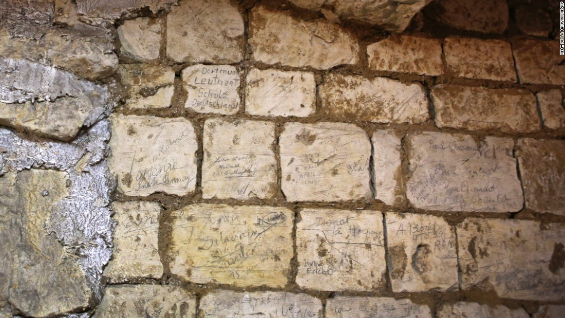 Names are engraved in on a wall in the former chalk quarry. The quarry mostly contains the names of Australian, British and American soldiers.