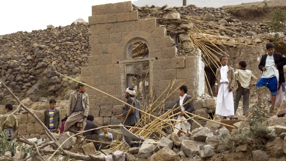 Yemenis gather as they search for survivors in the rubble of houses destroyed by Saudi-led airstrikes in a village near Sanaa, Yemen.