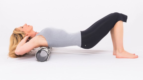 Lie on the roller with it positioned across your upper back. Keep both knees bent with your feet down and core engaged for support. Maintain a neutral neck position with your hands placed gently behind your head. Roll slowly from your upper back to the base of your ribcage. To increase intensity, cross your arms in front.