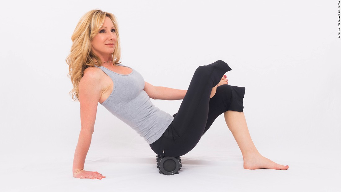 Sitting on the roller, bend your leg to bring your foot to the opposite knee. Place a hand on the floor for support. Lean your weight into the bent-knee side and slowly roll the entire glute area (back and outside of your hip). Pay special attention to releasing tension in your piriformis muscle (deep hip rotator), which is often responsible for sciatic nerve pain. Repeat on the other side.