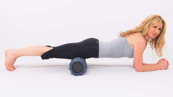 Take a forearm plank position with your quadriceps (thighs) resting evenly on the roller. Engage core muscles and walk your forearms forward and back for support as you roll from just below your hips to just above your knees.