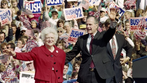 """President George H.W. Bush and first lady Barbara Bush wave to supporters on October 12, 1992, at a campaign rally in Springfield, Pennsylvania. Buttons and posters that read """"Stand by the President"""" and """"Let"""