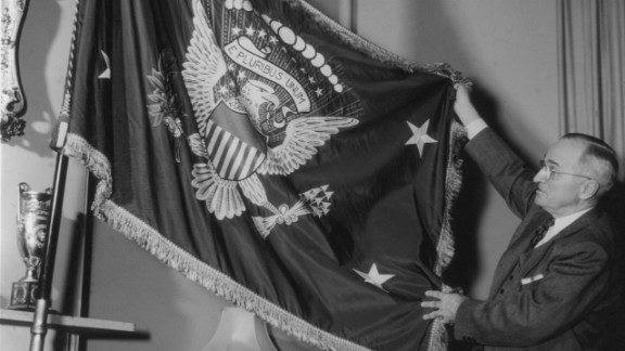 """Truman holds a flag bearing the Seal of the United States, circa 1945. Truman used the slogan, """"I"""