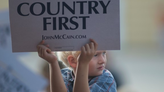 """A child holds up a """"Country First"""" sign while waiting for vice presidential candidate Alaska Gov. Sarah Palin and presidential nominee Sen. John McCain at a rally of supporters on September 18, 2008, in Cedar Rapids, Iowa."""