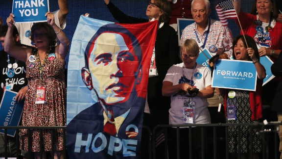 """People cheer as Obama speaks on stage as he accepts the nomination for president on September 6, 2012, in Charlotte, North Carolina. After his successful """"Hope and Change"""" 2008 campaign, Obama ran for reelection on the slogan """"Forward."""""""