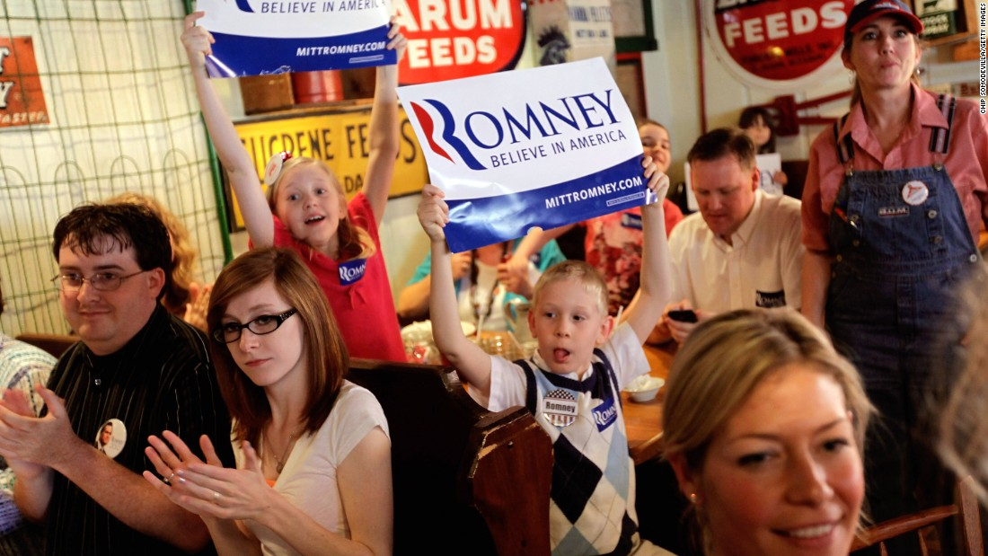 "Excited supporters cheer and hold up ""Believe in America"" signs as Romney arrives for a campaign stop in Rockford, Illinois, on March 18, 2012."
