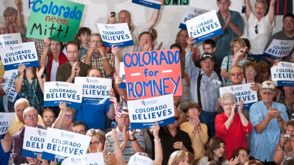 """People cheer as Republican presidential candidate Mitt Romney speaks at a town hall meeting in Grand Junction, Colorado, on July 10, 2012. Supporters hold up """"Colorado Believes"""" signs, based on Romney"""