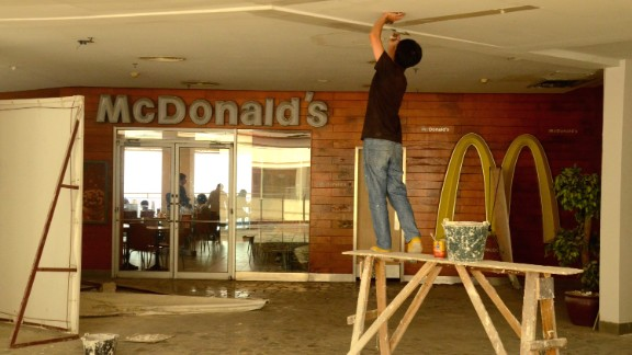A construction worker fixes a ceiling outside a McDonald