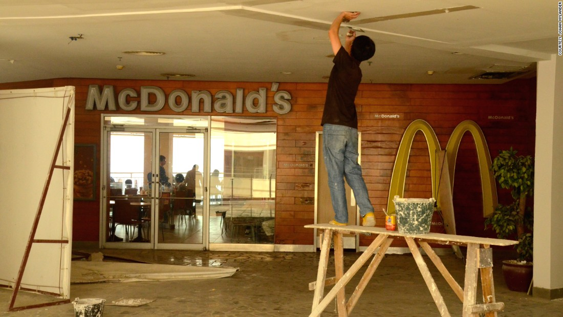 A construction worker fixes a ceiling outside a McDonald's restaurant,  New South China Mall. <br />