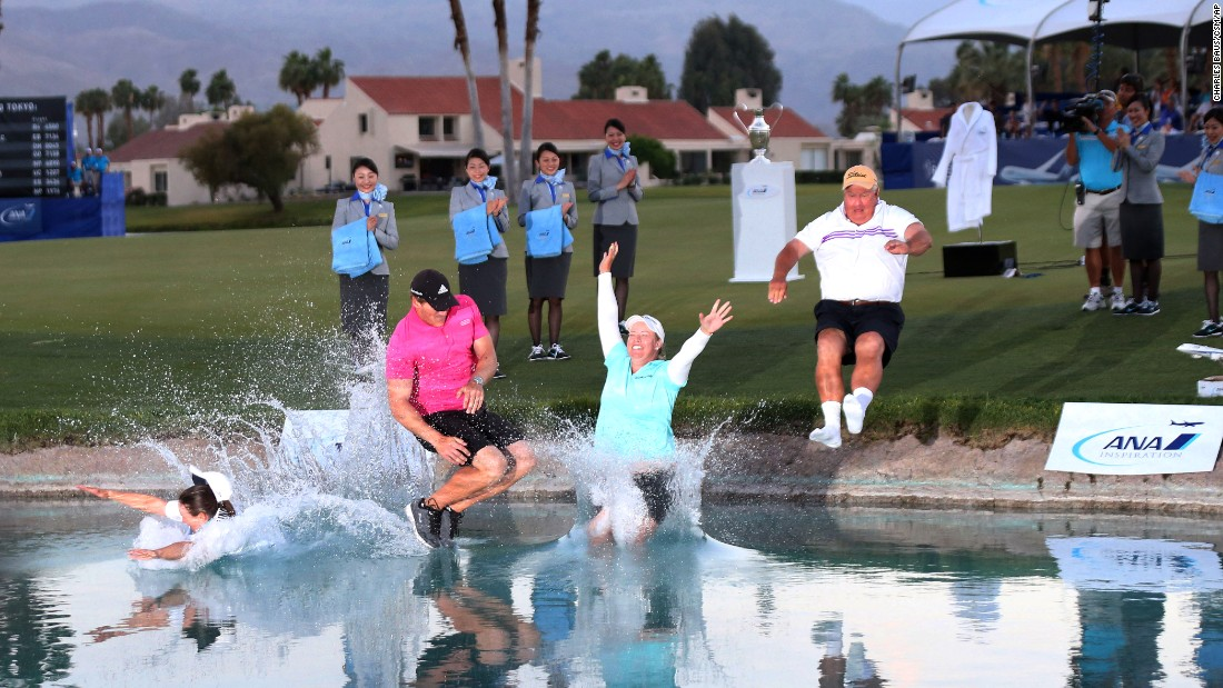 Pro golfer Brittany Lincicome, in the blue shirt, makes the traditional jump into Poppie's Pond after winning the ANA Inspiration tournament Sunday, April 5, in Rancho Mirage, California. It is the second career major for Lincicome, who was joined on the jump by her caddie, Missy Pederson; her fiance, Dewald Gouws; and her father, Tom Lincicome.