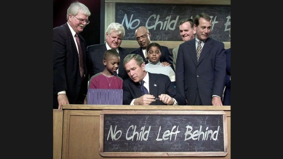 """President George W. Bush waves from the stage during a bill-signing ceremony for the No Child Left Behind Act during a visit to Hamilton High School in Hamilton, Ohio, on January 8, 2002. """"Leave No Child Behind"""" was a popular slogan during Bush"""