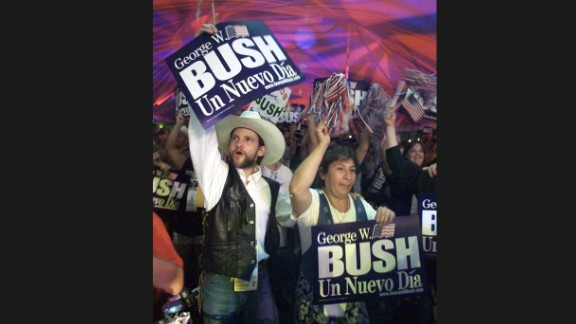 """Hispanic supporters of Bush cheer and hold up a sign that reads """"A New Day"""" in Spanish, after the Texas governor won the Republican Party"""