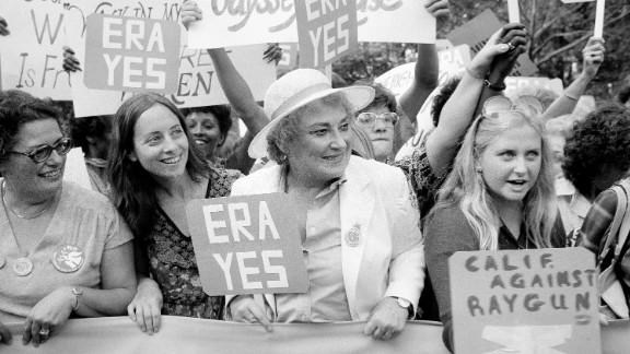Bella Abzug, center, smiles as she holds up an ERA sign on New York
