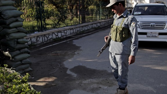 An Afghan policeman looks at a bloodstained pavement at the site of an attack by an Afghan national army soldier who opened fire on U.S. troops, at the compound of the provincial governor, in Jalalabad, Afghanistan on April 8, 2015.