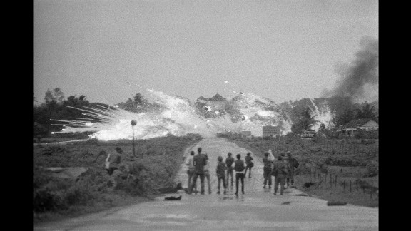 As bombs drop in Trang Bang, soldiers and members of the international media watch the scene in the foreground.