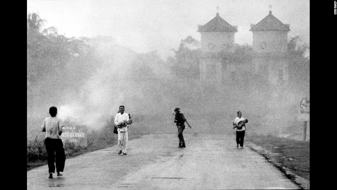 The aerial attack was intended for enemy forces on the outskirts of the village, but it accidentally hit South Vietnamese soldiers and civilians. Here, a man and woman carry injured children down the road following the bombing.