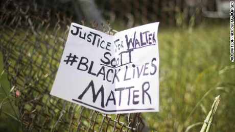 A placard is tied to a fence outside the vacant lot where Walter Scott, the 50-year-old man who was fired at eight times was killed as he ran away from an officer after a traffic stop in North Charleston, South Carolina on April 8, 2015. Police officer Michael Slager,33, who fatally shot Scott in the US city of North Charleston has been fired after he was charged with murder, the mayor said. Speaking at a highly charged press conference frequently interrupted by residents angered at America's latest high-profile police killing of a black man, Mayor Keith Summey said the city had moved quickly to fire the officer after Saturday's shooting.   AFP PHOTO/JIM WATSON        (Photo credit should read JIM WATSON/AFP/Getty Images)