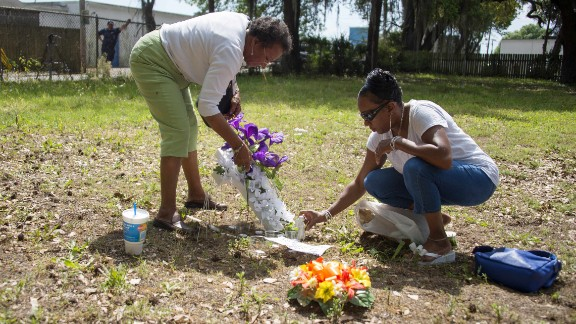 Scott's cousin Barbara, right, and her mother, Evaliana Smalls, lay flowers at the lot where the shooting took place.