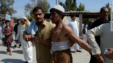 Afghan residents assist a wounded man after a suicide car bomb targeted a NATO convoy in Jalalabad.